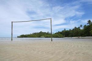 campo da calcio brasiliano vuoto sulla spiaggia con palo della porta foto