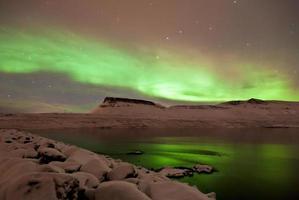 l'aurora boreale si arriccia sopra le montagne e il mare.