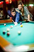 giovane coppia giocando a biliardo foto