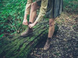 donna che lega le sue scarpe nella foresta foto