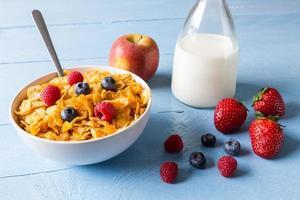 cornflakes in una ciotola con latte e frutta foto