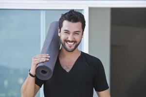 uomo sorridente che tiene una stuoia di yoga foto