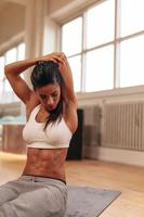 giovane donna muscolare che allunga le braccia foto