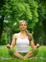 donna che si siede nella meditazione di posa di yoga all'aperto foto