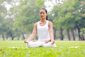 bella donna a praticare yoga nel parco foto
