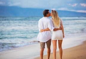 coppia godendo il tramonto sulla spiaggia foto