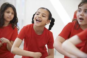 gruppo di bambini che godono insieme della lezione di ballo foto