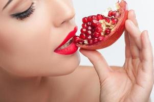 la giovane donna attraente sta godendo della frutta sana foto