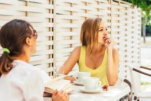 due amiche che si godono nel caffè estivo foto