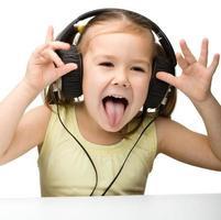 bambina sveglia che gode della musica usando le cuffie foto