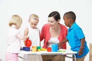 bambini in età prescolare che si godono il tea party con l'insegnante foto
