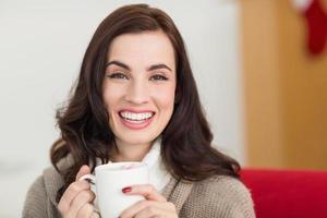 brunette sorridente che gode di una cioccolata calda con la caramella gommosa e molle foto