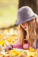 giovane donna che legge un libro e che gode dell'autunno foto