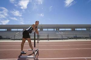 atleta maschio appoggiando le braccia sull'ostacolo, vista laterale (riflesso lente)