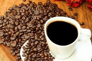 tazza di caffè e fagioli su uno sfondo di legno.