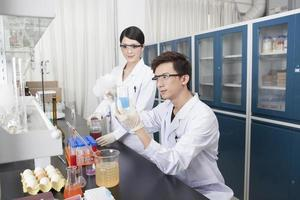due giovani coltivano esperimenti di ricerca scientifica foto
