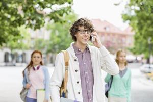 giovane studente maschio sorridente che per mezzo del telefono cellulare con gli amici