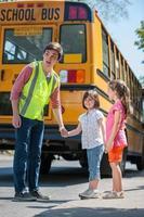 la guardia di attraversamento degli studenti più grandi aiuta i giovani studenti elementari foto