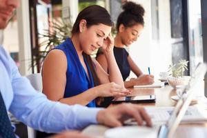 donna di affari che utilizza compressa digitale nella caffetteria