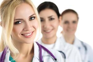 Ritratto di giovane dottoressa bionda circondata da tè medico foto
