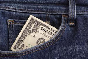 una banconota da un dollaro in una tasca di jeans blu foto