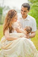 madre l'allattamento al seno bambino con il marito in spazi aperti romantici foto