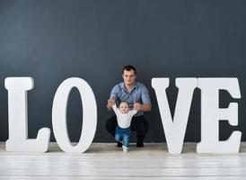 padre felice che trasportano figlio isolato su sfondo grigio