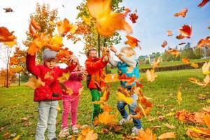 un gruppo attivo di bambini gioca con foglie volanti