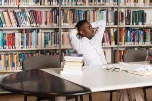 studente maschio confuso che legge molti libri per esame foto