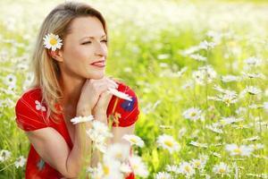 donna sorridente nel campo della margherita selvatica foto