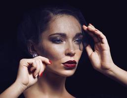 bellezza donna bruna sotto il velo nero con manicure rosso vicino