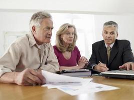 coppia con consulente finanziario al tavolo foto
