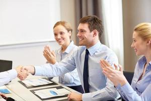 squadra sorridente di affari che stringe le mani in ufficio foto