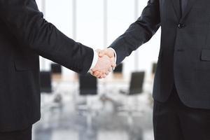 gli uomini d'affari si stringono la mano nella sala conferenze foto