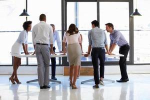 colleghi in piedi intorno a un tavolo da conferenza foto
