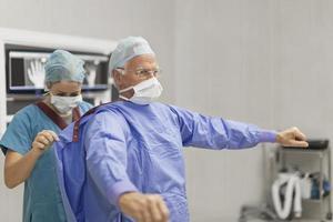 infermiera mettendo cappotto sul chirurgo foto