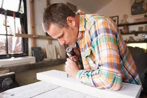 muratore di pietra al lavoro sulla scultura in studio foto