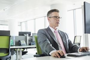 uomo d'affari maturo che lavora al computer in ufficio foto
