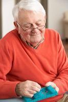 uomo senior di smistamento dei farmaci utilizzando organizzatore a casa foto