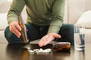 uomo che mostra le pillole e che tiene la bottiglia da birra