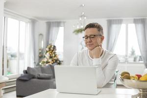 uomo sorridente che per mezzo del computer portatile a casa
