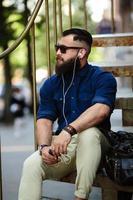 uomo barbuto seduto sulle scale foto
