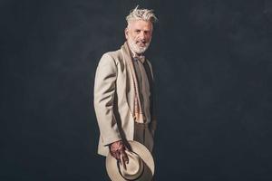 uomo barbuto senior alla moda contro la parete nera foto