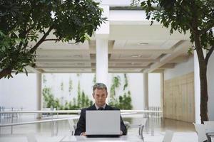 uomo d'affari che utilizza computer portatile al caffè dell'ufficio foto