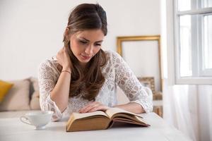 donna affascinante che si siede dalla tavola di legno e dal libro di lettura foto
