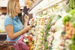 donna che legge la lista della spesa in un supermercato