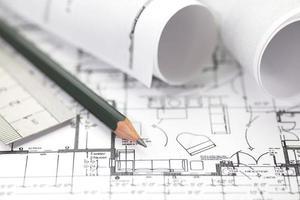 l'architetto rotola e progetta il disegno del progetto di costruzione foto