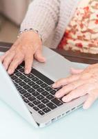 anziana della mano del primo piano che per mezzo del computer portatile foto