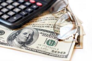 calcolatrice, dollari e occhiali foto
