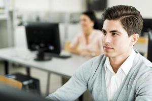 giovane uomo bello che studia tecnologia dell'informazione in un'aula foto